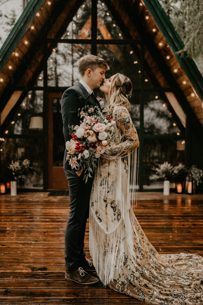 The bride was wearing a unique cream and sheer wedding dress with floral prints and embroidery and fringe