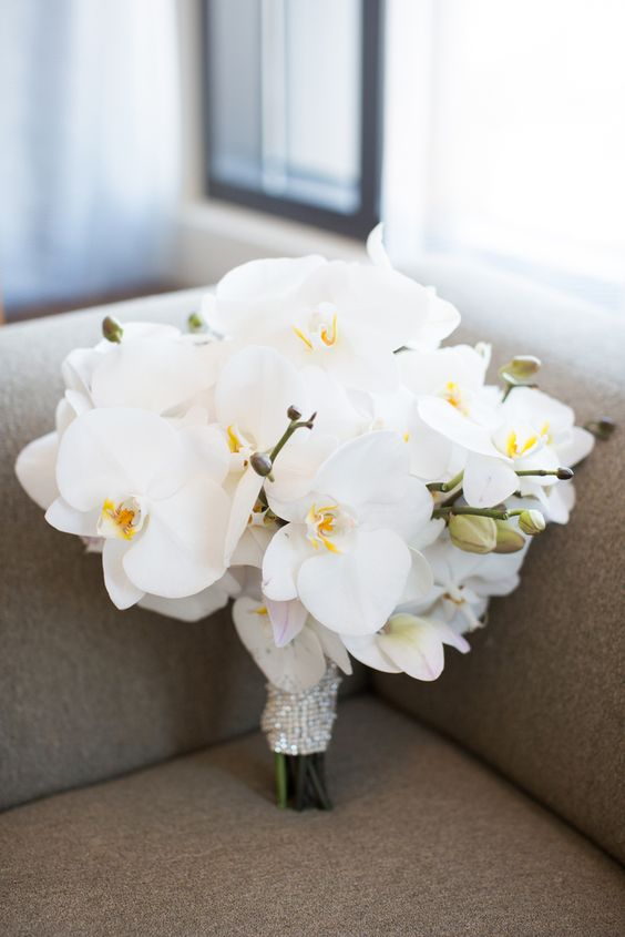 a glam wedding bouquet of white orchids and with a sparkling wrap is a timeless solution for every girl