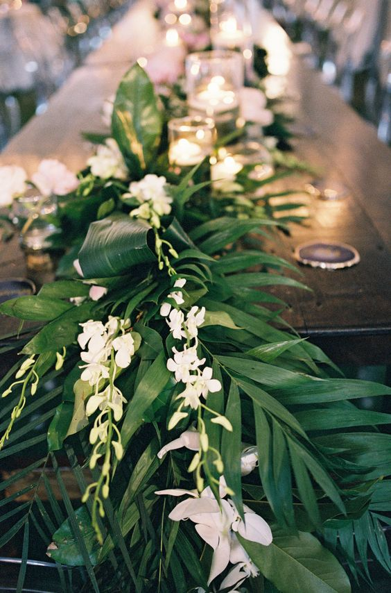 a lush and elegant table runner of greenery and white blooms plus floating candles