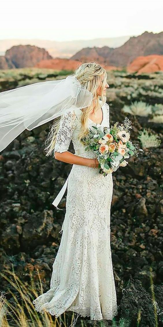 a sheath lace wedding dress with short sleeves and a V-neckline, a sash and a veil for a boho feel