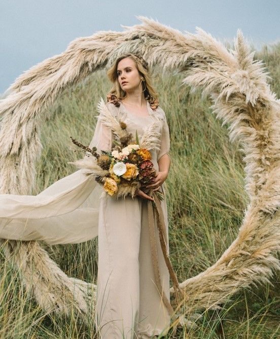 a taupe bridal jumpsuit with a cape and a taupe pampas grass circle wedding arch