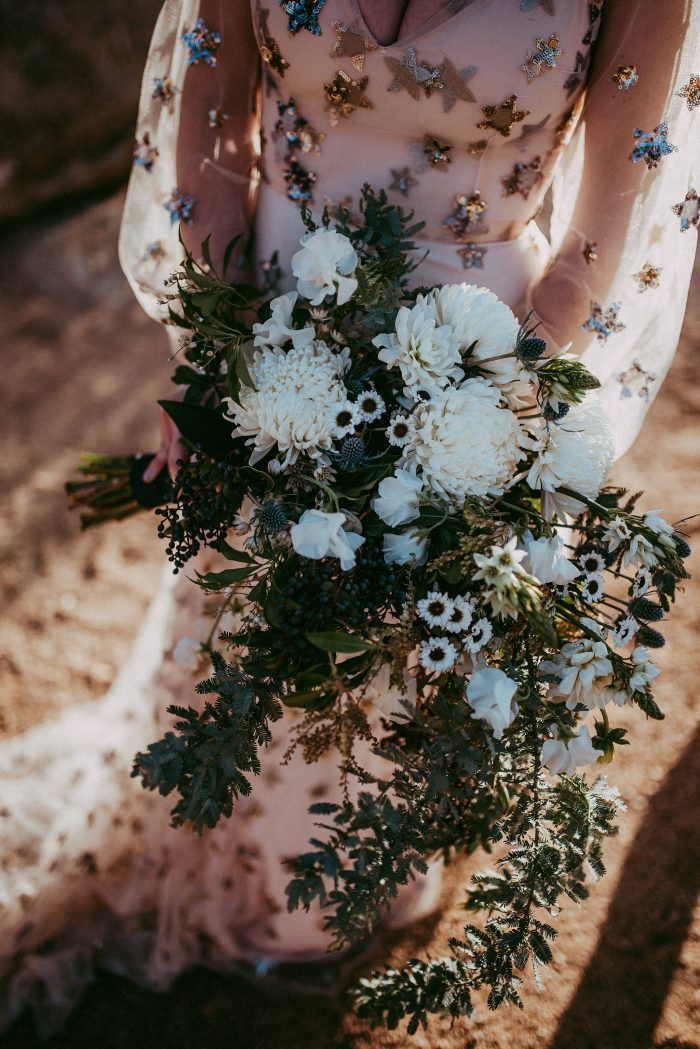 The wedding bouquet was done with greenery, white flowers and blue thistles and was cascading