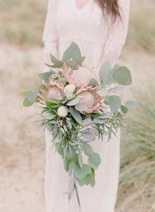 a delicate wedding bouquet with eulcayptus, king proteas and succulents for a textural and bold look