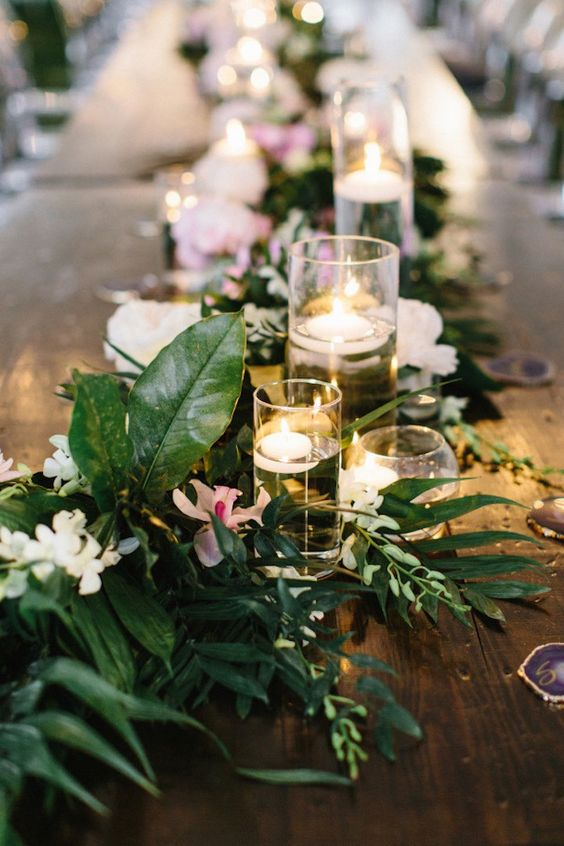 a greenery tropical table runner with white and pink blooms plus floating candles in candle holders