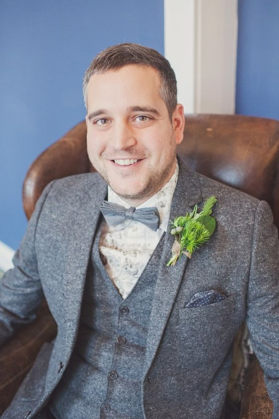 a grey wool three-piece suit, a grey bow tie and a light floral printed shirt for a whimsy touch