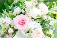 05 a lush and fresh centerpiece with white and pink roses, daisies and greenery in a gold bowl