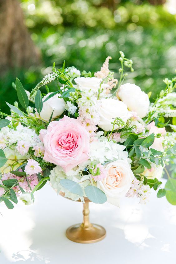 a lush and fresh centerpiece with white and pink roses, daisies and greenery in a gold bowl