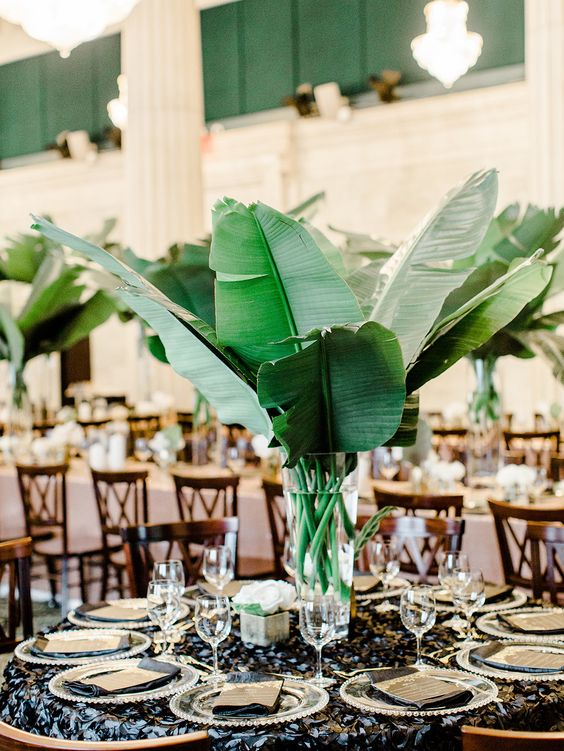 a modern centerpiece with large banana leaves and a clear vase   DIY them all