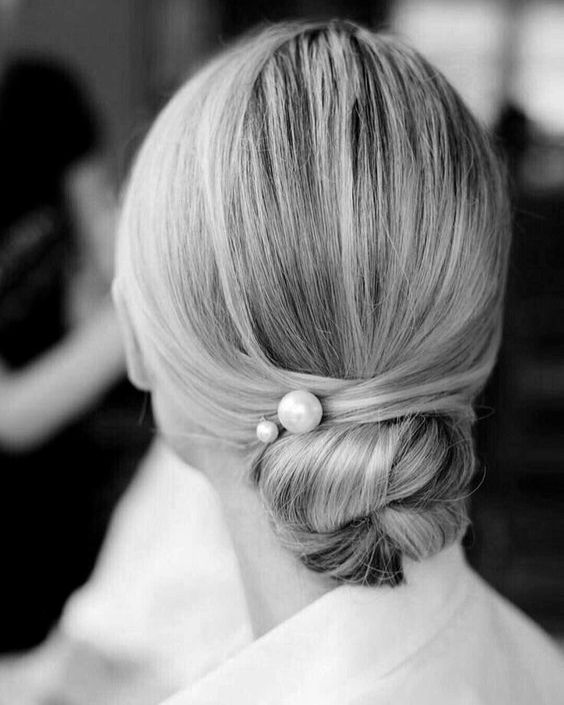 a modern sleek twisted chignon with pearl hairpins for a gorgeous and elegant minimalist bride