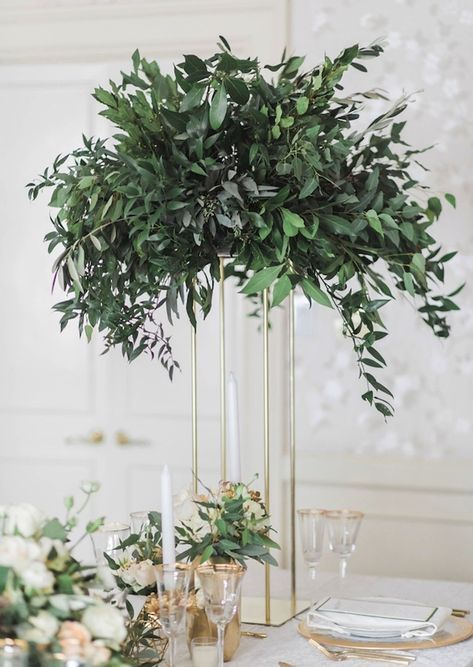 a tall centerpiece on a gold stand with lush greenery is an elegant modern idea