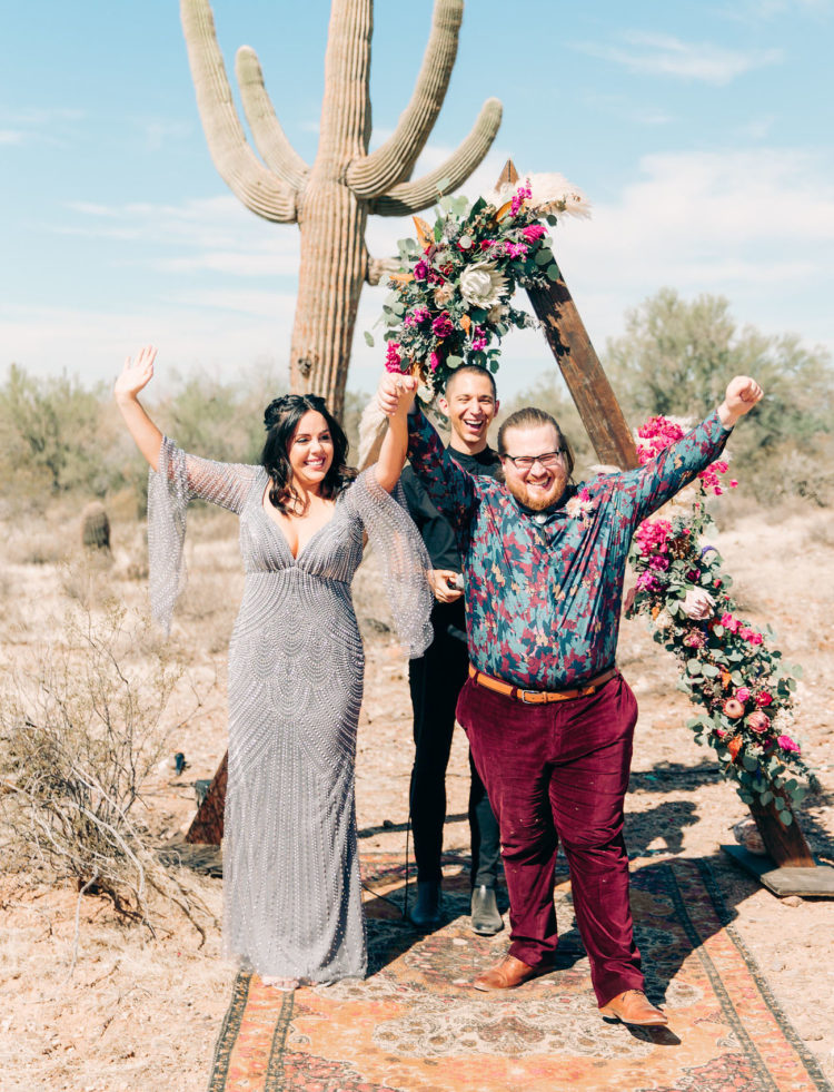 The groom was wearing plum-colored velvet pants, a bright floral shirt, amber shoes and a belt