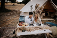 06 The wedding picnic was styled with a small wooden table, pampas grass and black plates