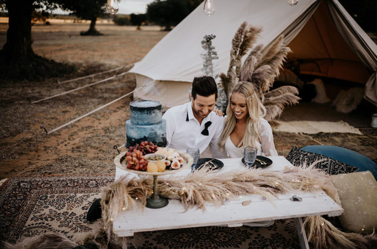 The wedding picnic was styled with a small wooden table, pampas grass and black plates