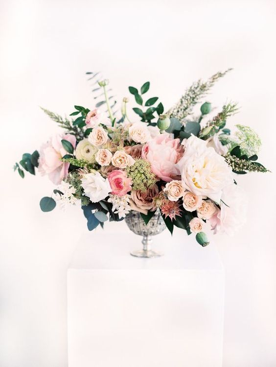 a super lush and textural floral centerpiece with blush, pink and white blooms, herbs and greenery