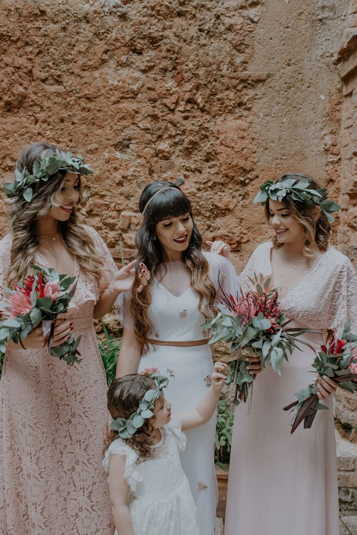 The bridesmaids were rocking blush lace gowns and greenery crowns