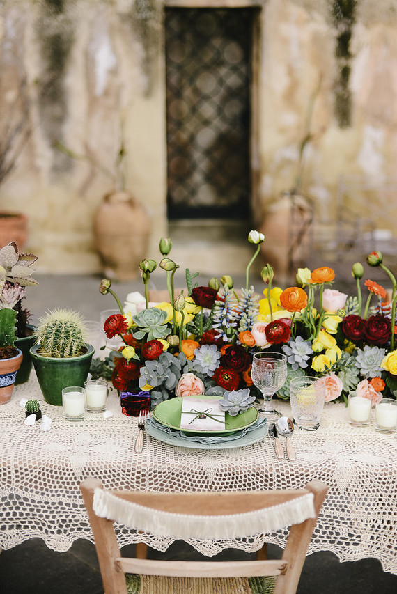 The wedidng tablescape was done with bright florals, a macrame tablecloth, candles and cacti