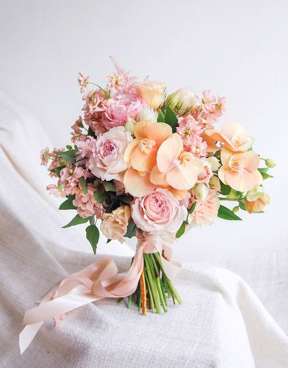 a beautiful and sweet pastel bouquet of pink garden roses and peachy orchids for a spring or summer bride