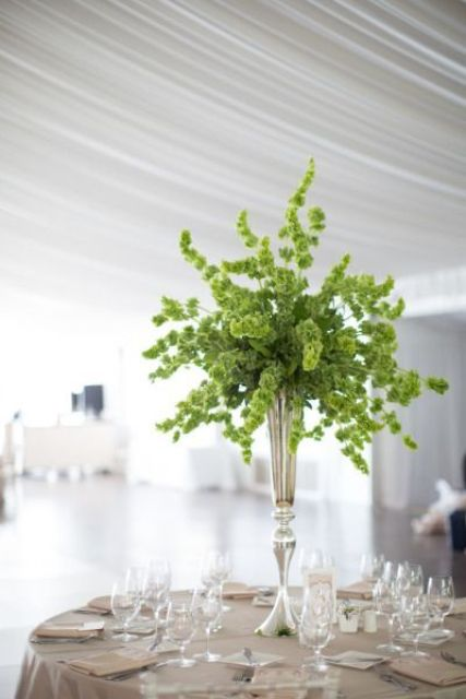 a bold greenery wedding centerpiece in a silver vase is a chic and organic idea to rock