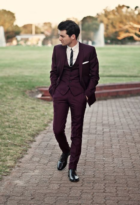 a gorgeous three piece plum colored suit with a narrow striped tie, black shoes and a white shirt