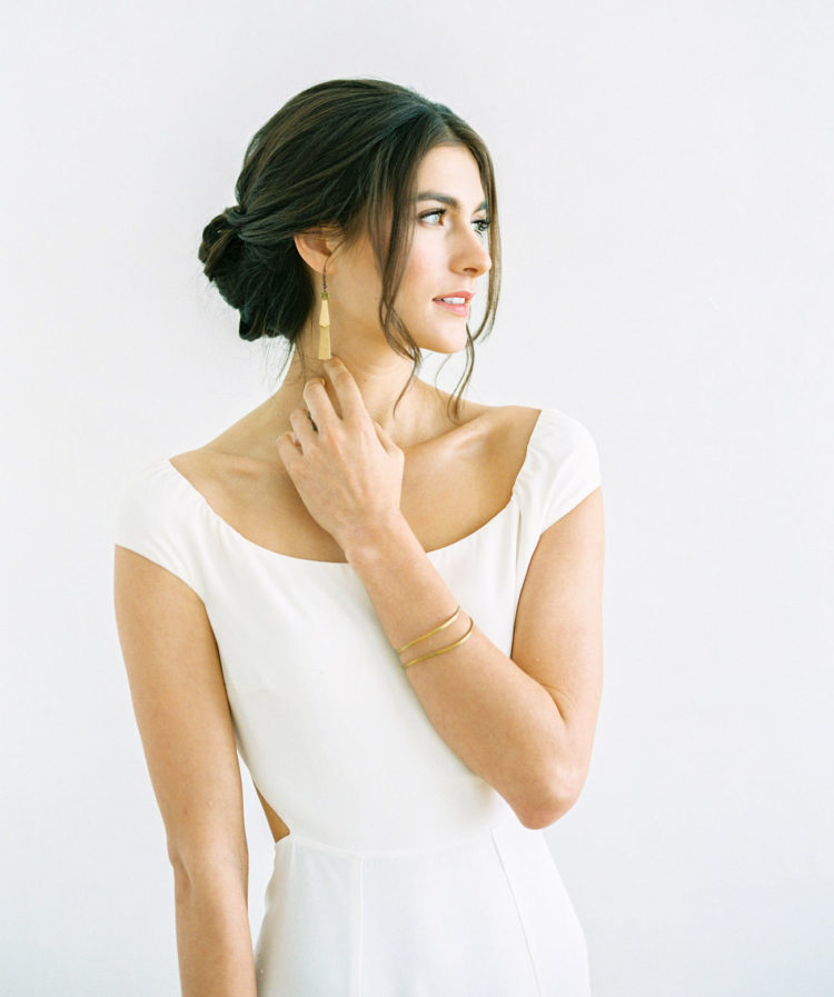 a low twisted bun hairstyle with a sleek top and some bangs is a chic and refined idea for a minimalist wedding