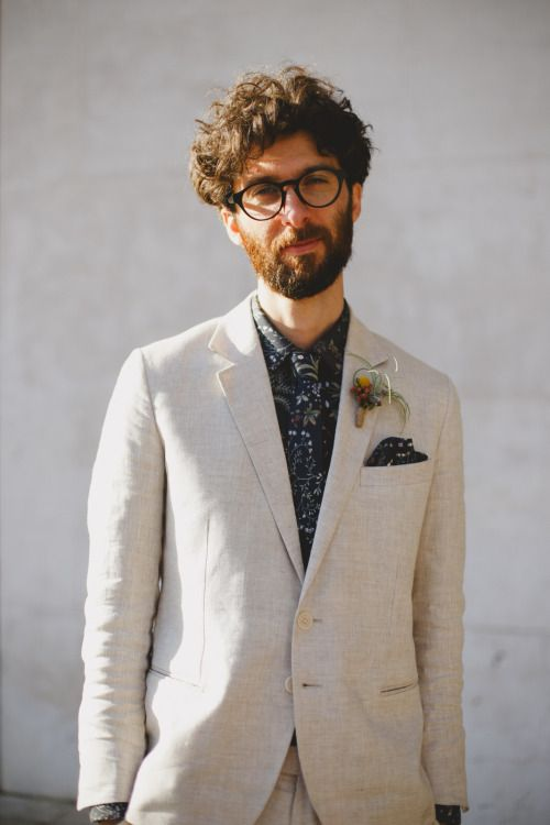 an unconventional look with a creamy suit, a dark floral tie and shirt plus an air plant boutonniere