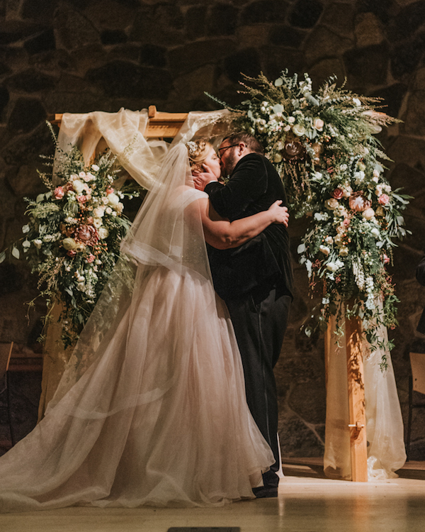 The wedding arch was done with blush tulle, lush florals and greenery