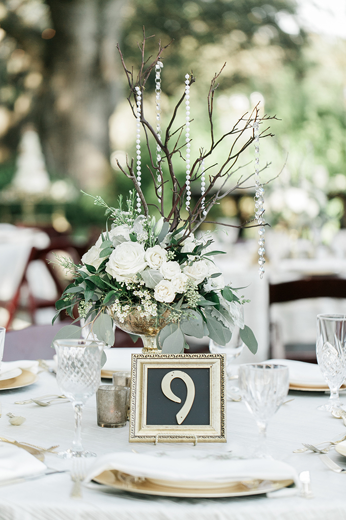 The wedding reception tables were done wih white roses, greenery, hanging crystals and gilded touches