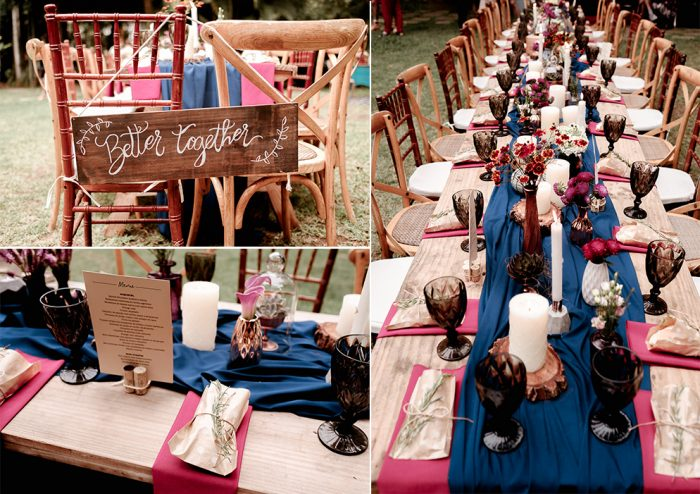 The wedding table settings were done with marsala napkins, blue table runners, blooms, candles and black glasses