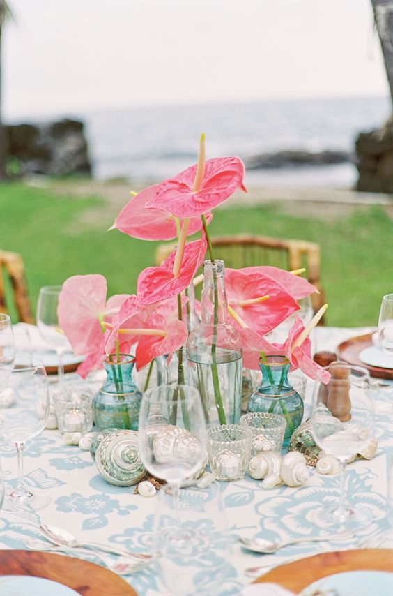 a bold tropical beach wedding arrangement with shells, clear glasses and vases and pink bloom