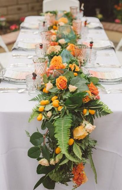 a lush greenery tropical runner with citrus and orange blooms to match