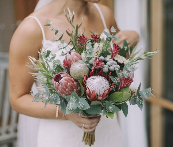 a summer wedding bouquet with king proteas, greenery, berries and seeded eucalyptus for a creative look