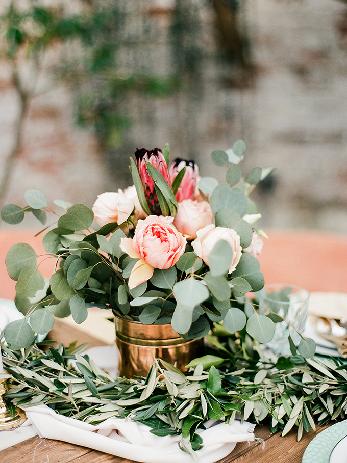 Fresh eucalyptus, olive branches, pink roses and pink proteas were main florals