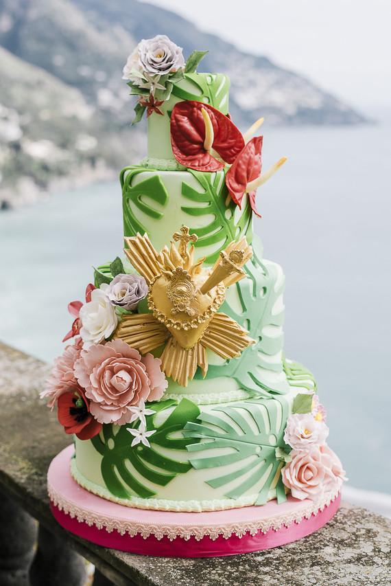 The wedding cake was done with tropical leaves, sugar blooms, tropical flowers and a gold heart