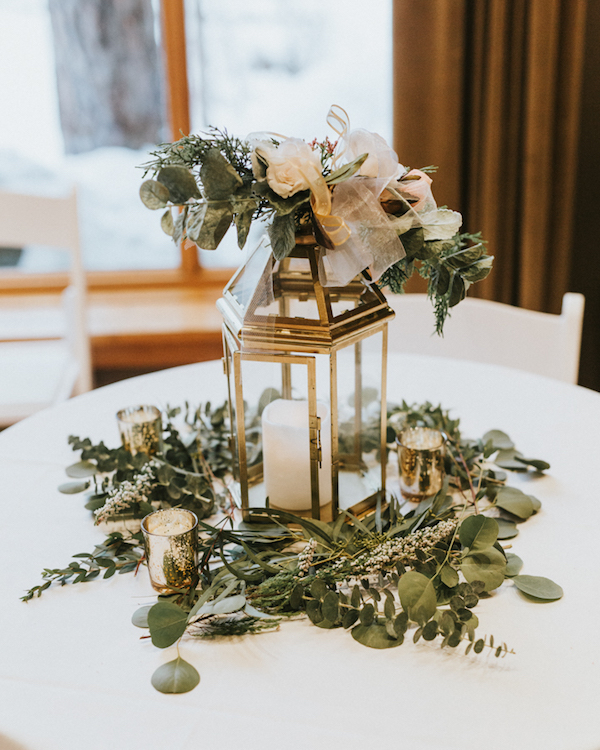 The wedding tables were done with candle lanterns, lots of greenery and blooms