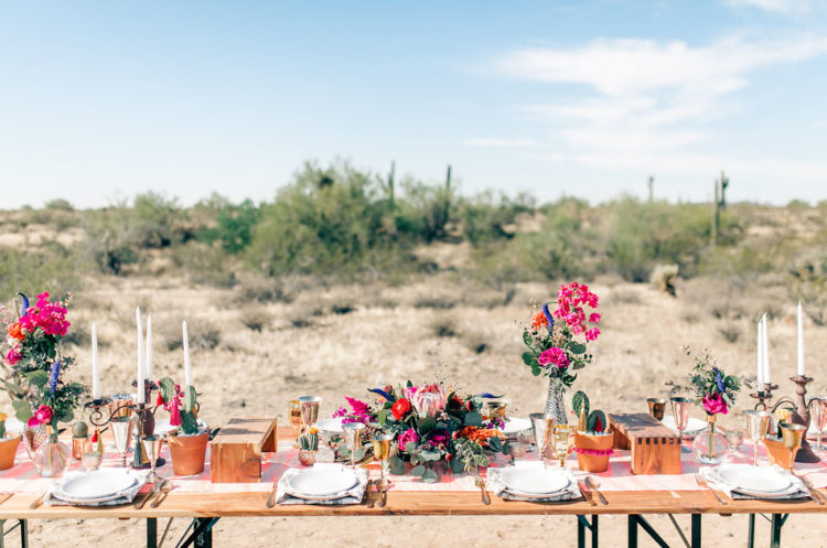 The wedding tablescape was done with hot pink blooms, candles, gilded touches and wooden accessories