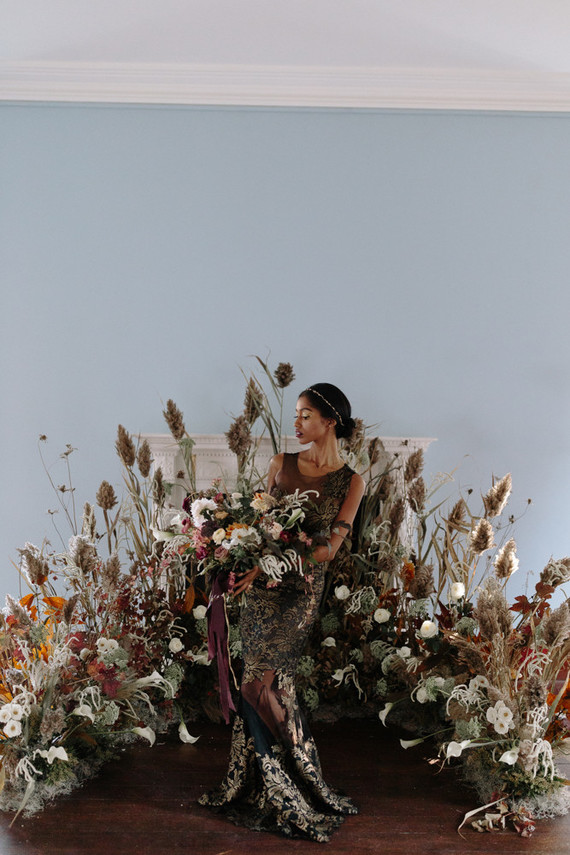 This oversized semi circular flower and herb altar was a perfect fit for the shoot, and the black and gold sheath wedding dress strikes at once