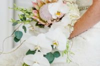09 a cascading tropical wedding bouquet with white orchids, greenery and a king protea for a bold statement