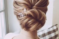09 a chic and voluminous bridal chignon hairstyle with a wavy bump on top and a little floral hairpiece