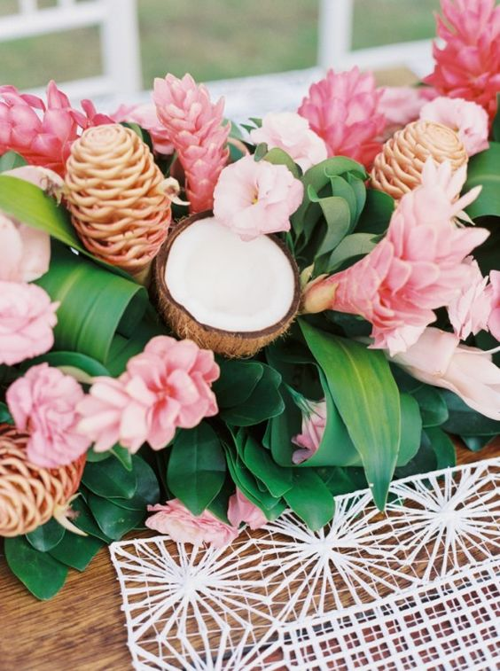 a lush tropical table runner ith leaves, pink blooms and coconuts looks very exotic