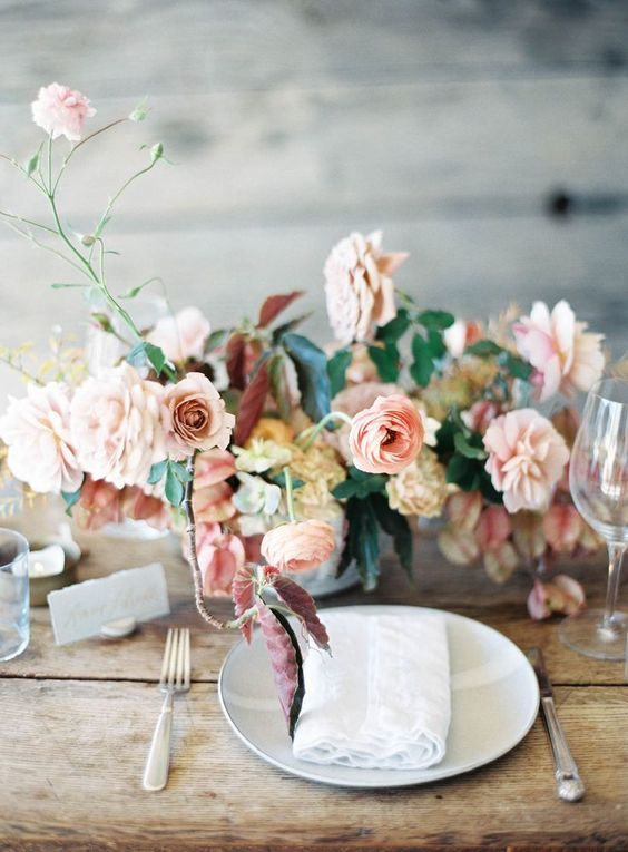 a pastel wedding centerpiece with blush and light-colored mauve blooms with greenery