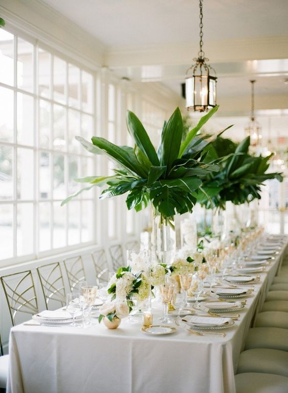 tall centerpieces in clear glass vases with palm leaves are great for a southern or tropical wedding