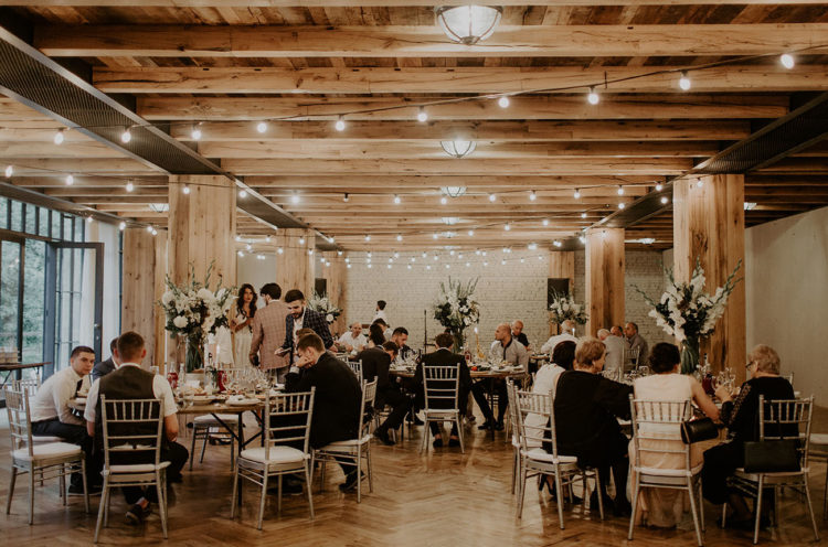 The wedding reception was rustic, illuminated with lights and with lush floral centerpieces