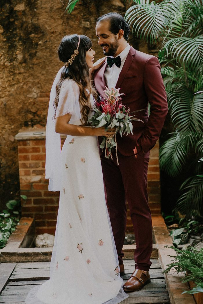 a burgundy suit, a black velvet bow tie, amber colored shoes for a tropical groom