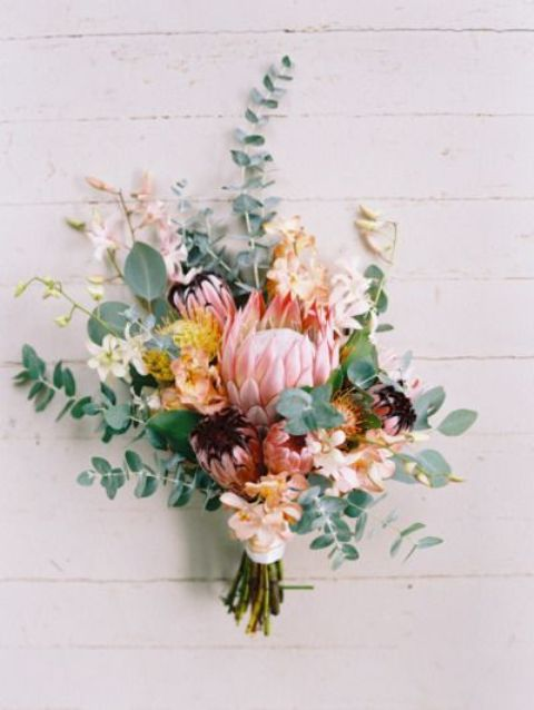 a chic and textural bouquet with king proteas, eucalyptus, blush and white blooms for a lush look