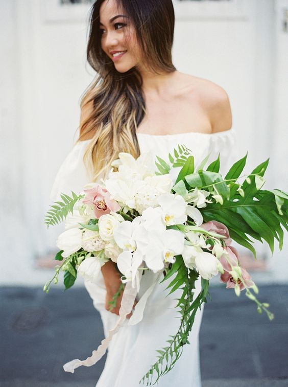a chic cascading bouquet with white and light pink orchids and greenery for a romantic feel