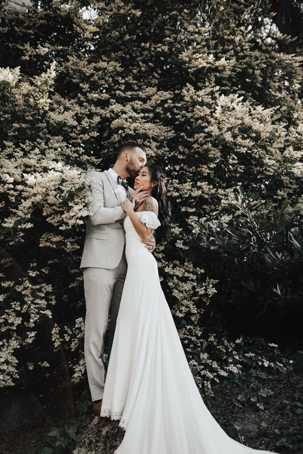 a gorgeous mermaid off the shoulder wedding dress with a lace trim and a long train for an ethereal look