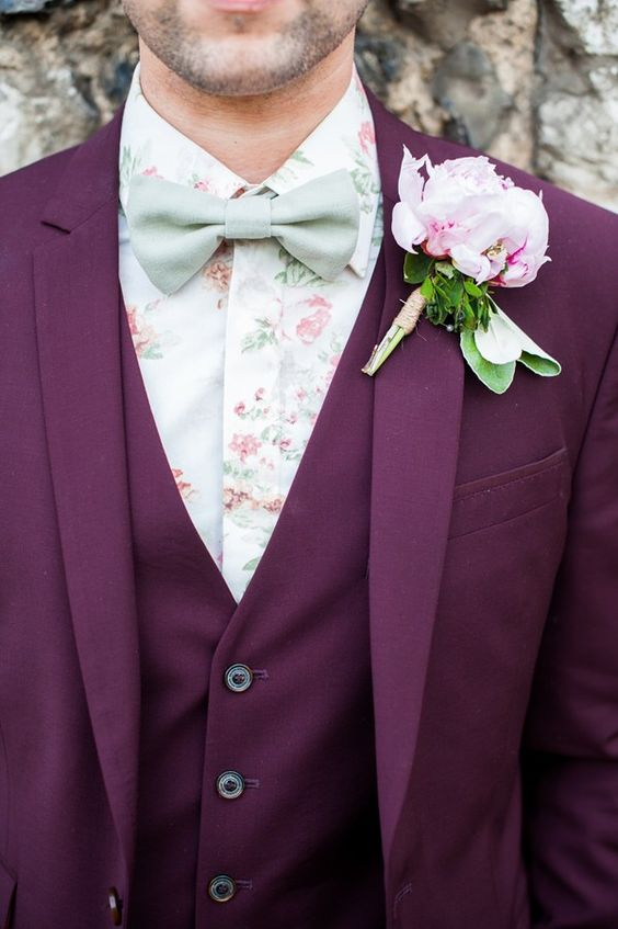 a whimsy groom's outfit with a burgundy three-piece suit, a floral print shirt, a matching green bow tie