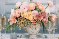 10 an ombre floral centerpiece with pink, mauve and yellow blooms, greenery and berries