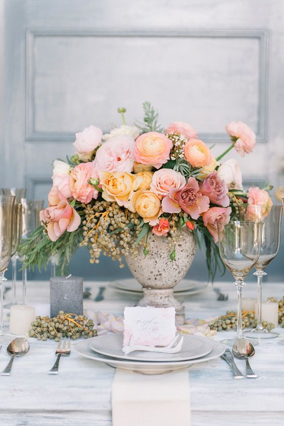 an ombre floral centerpiece with pink, mauve and yellow blooms, greenery and berries