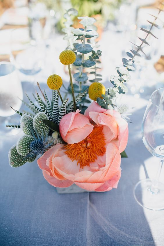 a bold centerpiece with a pink bloom, succulents, cacti, eucalyptus and billy balls